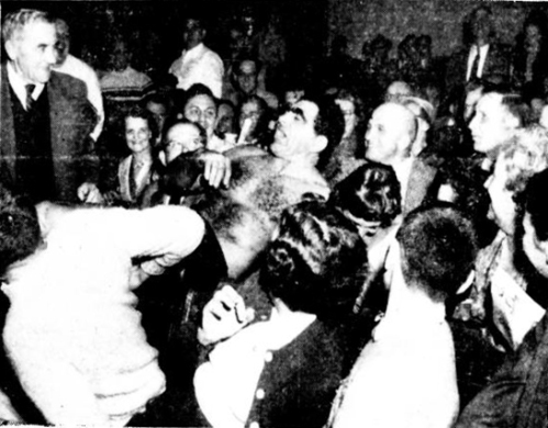 TIT FOR TAT…  Hartford-born wrestling sensation Bull Curry, who spent the evening tossing his opponent out of the ring, lands in the third row after fans in foreground ducked neatly to one side to give him room.  But the Bull, even though he may not look it here was a winner.